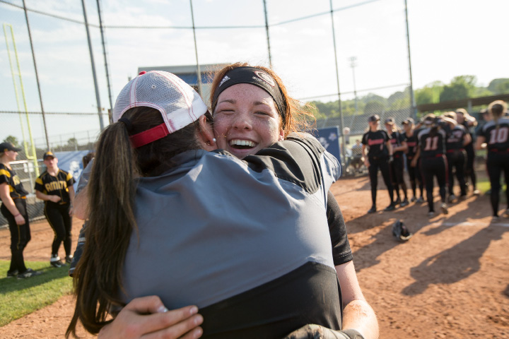 Game MVP and winning pitcher Abby Abramson (smiling) gets a congratulatory hug from coach Kristine Drust after Saturday's victory.