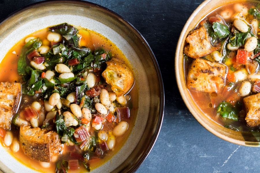This image released by Milk Street shows a recipe for Tuscan Soup. Milk Street kitchens start from scratch with ciabatta croutons and canned white beans. Sturdy greens such as red-veined Swiss chard add color and texture from crispy stems. They are sautéed with onions and bell pepper. If you like, serve the soup topped with grated Parmesan cheese. (Milk Street via AP)