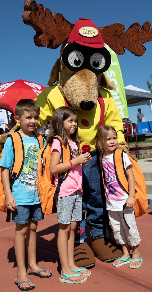 Left to right, Joseph Lewis, 7, and sisters Sophia, 6, and Abigail, 4, all of Meriden, sport their new backpacks with Elroy the Elk during the Meriden Fire Local 1148 annual Back-to-School Expo on the Meriden Green, Tues. Aug. 20, 2019. Elroy the Elk is the mascot for the Elks National Drug Awareness Program. Dave Zajac, Record-Journal