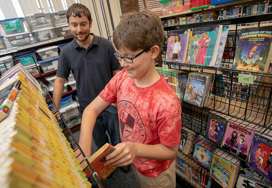 Lucas Cotter, 11, of Meriden, looks for a Goosebumps series book to take out next to father, Jacob, while in the Children