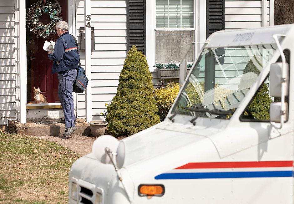 A USPS postal carrier delivers mail to a residence on Baldwin Avenue in Meriden, Wed., Apr. 1, 2020. Dave Zajac, Record-Journal