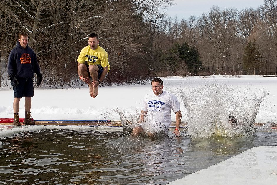Members of Team Southington BOE jump into the frigid waters of Sloper Pond Saturday afternoon during the 6th Annual YMCA Camp Sloper Polar Plunge in Southington, Jan. 22, 2011. At left, Mark Pooler, director of Camp Sloper, observes the plunge. (Christopher Zajac/Record-Journal)