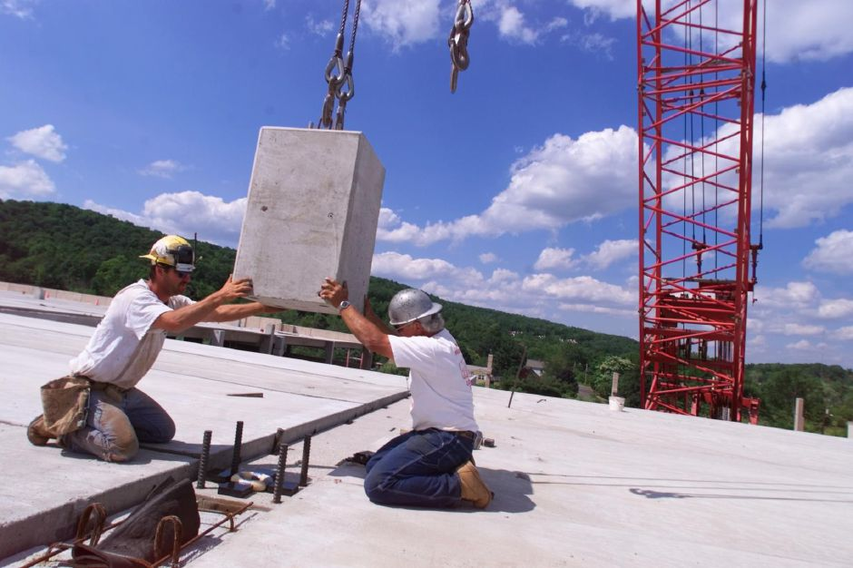 RJ file photo - Bill Selengo of Guliford and Mike Piscitelli of West Haven, iron workers with Guilford-based Taylor Erectors, put a crane hoisted light post stub column in place atop the soon-to be completed parking garage at Meriden Square, June 15, 1999. The new parking garage is part of the mall