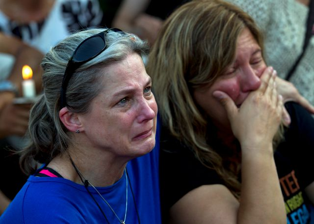 Carol Geithner, left, and Yasemin Jamison gather for a candlelight vigil across the street from where five journalists were slain in their newsroom in Annapolis, Md., Friday, June 29, 2018. Prosecutors say 38-year-old Jarrod W. Ramos opened fire Thursday in the Capital Gazette newsroom. (AP Photo/Jose Luis Magana)