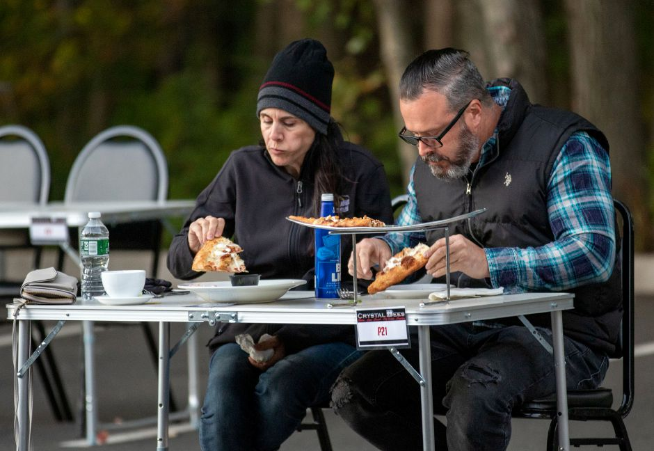 Naugatuck residents Steven and Lisa Leblanc bundle up as they enjoy a pizza during a concert at Crystal Bees on Friday, Sept. 18.