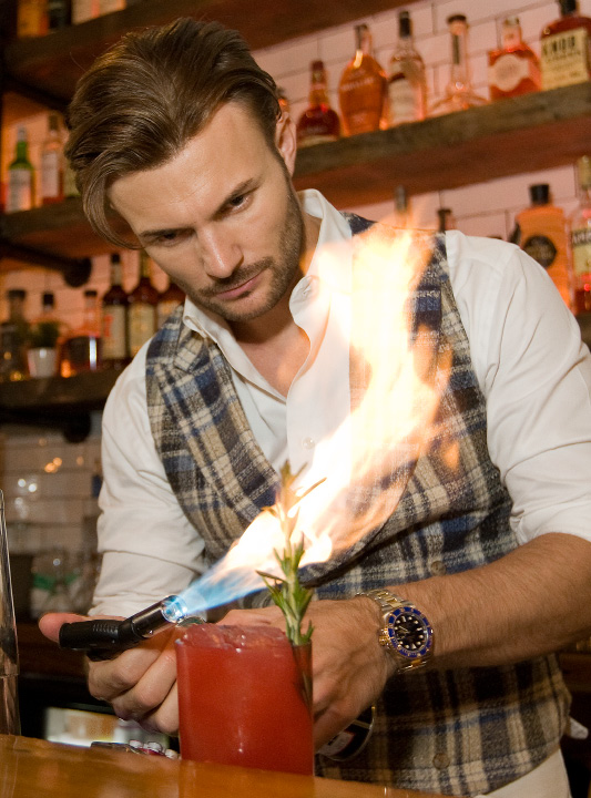 Ryan Tunnacliffe, general manager of Ideal Tavern in Southington, fires up a 'Bramble On' cocktail at the new restaurant on Center Street in Southington, Thursday, August 25, 2016. The drink is made with gin, blackberry and rosemary syrup, fresh lemon juice, and garnished with rosemary soaked in Absinthe. The rosemary garnish is fired with a torch for aromatic appeal.   | Dave Zajac, Record-Journal