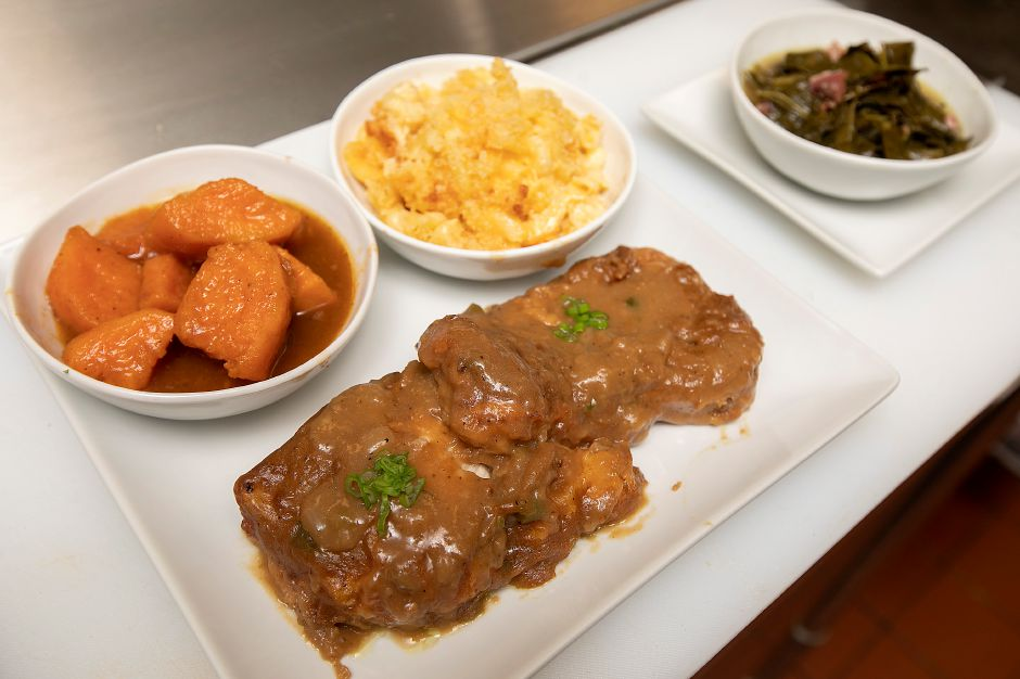 Smothered pork chops with sides at Americansoul Kitchen Bar.