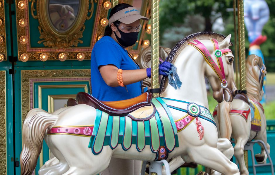 Kiddie Carousel attendant Nayelie Arroyo, wipes down the horses between rides at Lake Compounce on Tuesday, July 7, 2020. Aaron Flaum, Record-Journal