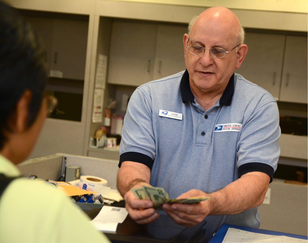 Meriden United States Postal Service clerk Gene Kirstens assists a customer at the post office on Thursday, June 15, 2017. | Bryan Lipiner, Record-Journal