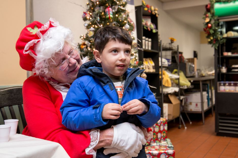 Vincent Cappola, of Southington, sits with Mrs. Claus, Cindy Miller, of Southington, at Paul Gregory