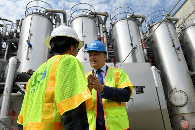 Democratic Presidential candidate Washington Gov. Jay Inslee, right, talks with Ryu Suzuki, left, as he tours the Blue Plains Advanced Wastewater Treatment Plant in Washington, Thursday, May 16, 2019, during an event where he unveiled part of his plan to defeat climate change. (AP Photo/Susan Walsh)