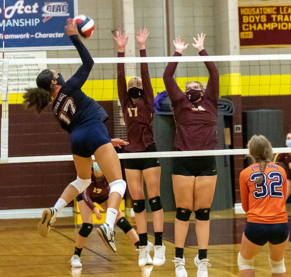 Lyman Hall's Mackenzie Grady spikes the volleyball past Sheehan's Gretchen Seibt and Caitlyn Hunt at Sheehan High School in Wallingford on Friday. The Lady Trojans won by game scores of 25-21, 25-19, 20-25 and 25-22.