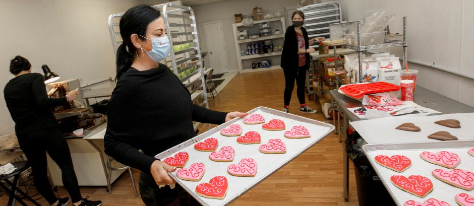 Rachael Ceste, owner of Sweet Cioccolata, carries a tray of freshly-made heart shaped cookies Thursday as the business continues creating a variety of sweets for Valentine's Day. Dave Zajac, Record-Journal