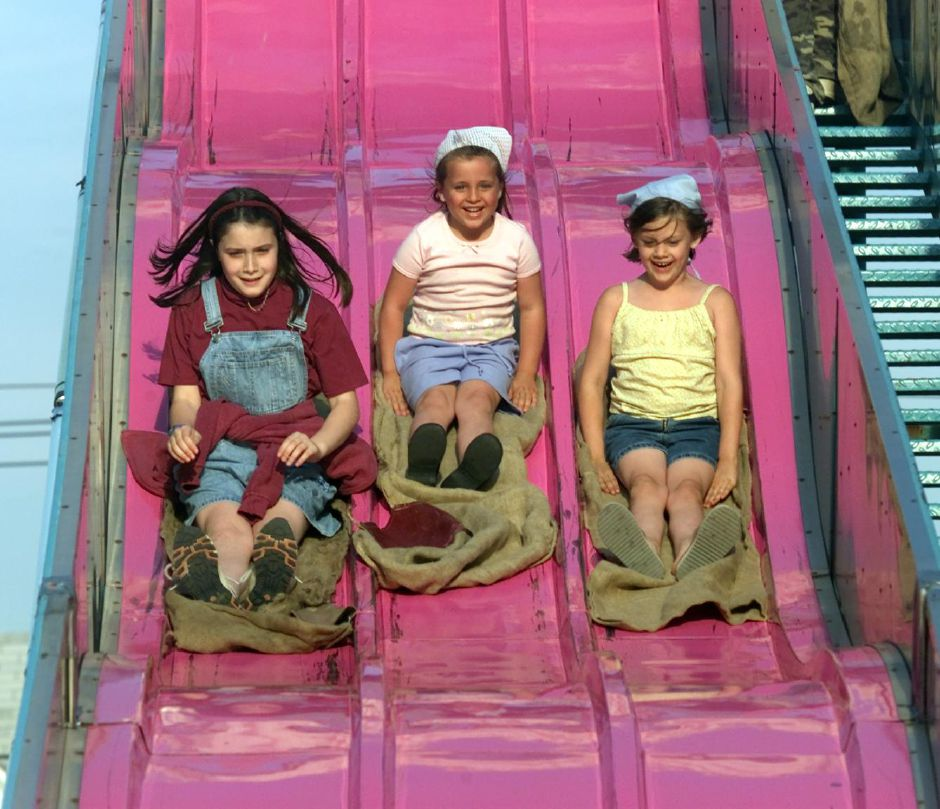 Sliding down the Slide ride, are Kelly Tartaglia, 11, left, Joelle Pisani, 5, center, and Samantha Beaudoin, 6, right, at the Holy Trinity Bazaar Thurs., June 8, 2000.