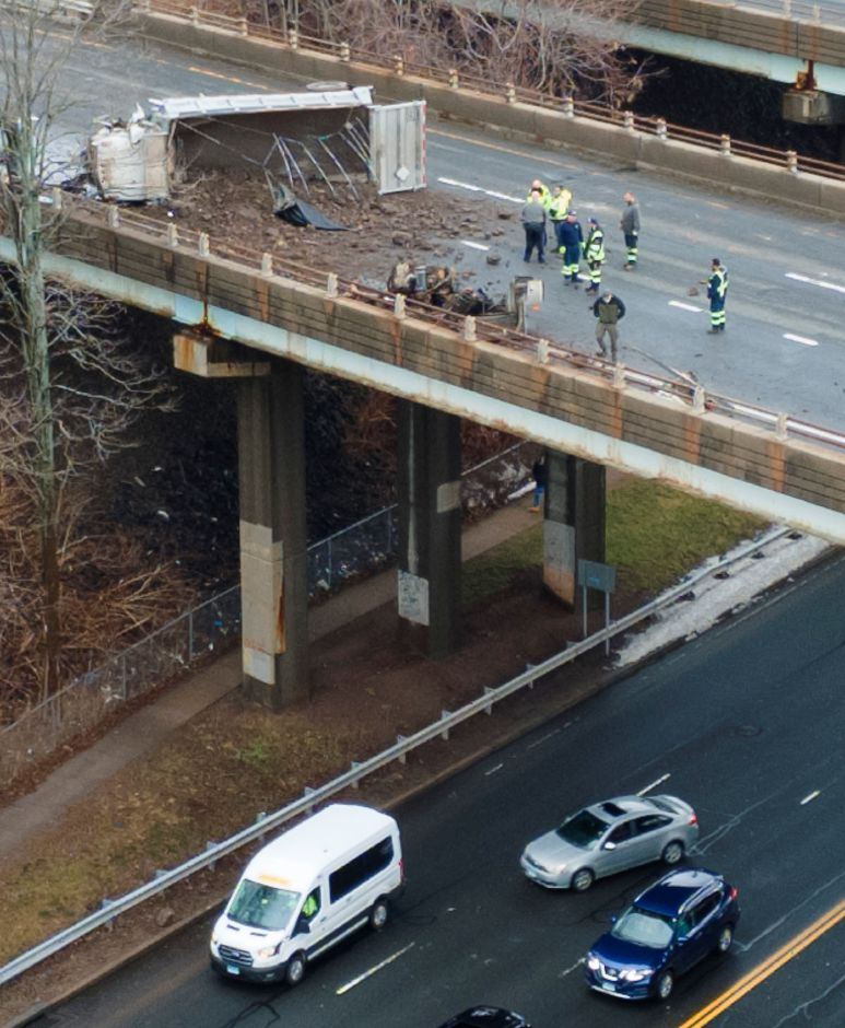 Emergency service crews work to clean up an overturned dump truck on Interstate 691 eastbound near Lewis Avenue in Meriden March 1, 2021. Dave Zajac, Record-Journal