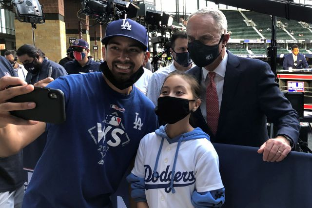 Major League Baseball Commissioner Rob Manfred poses with fans before Game 1 of a baseball World Series Tuesday, Oct. 20, 2020, in Arlington, Texas. Manfred said he hopes to keep two of this year