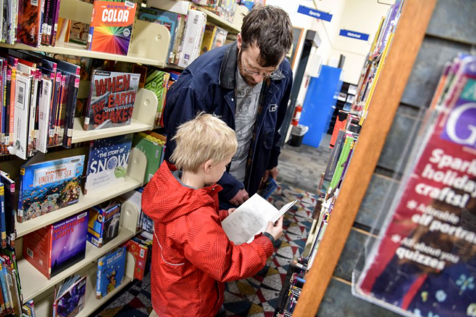 Henry Churchill helps his son Morgan, 6, pick out some books in the children