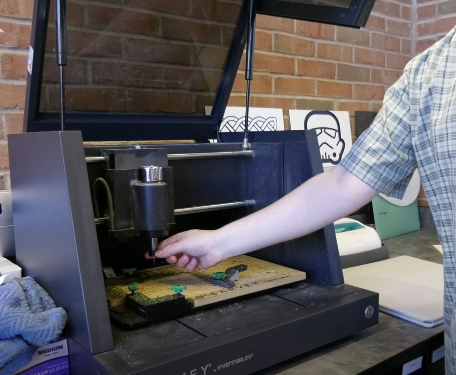 Max Spurr, creative technologies librarian, demonstrates an engraving machine in the collaboratory area of the Wallingford Public Library, 200 North Main St.. See more photos at www.myrecordjournal.com.  Ashley Kus, Record-Journal