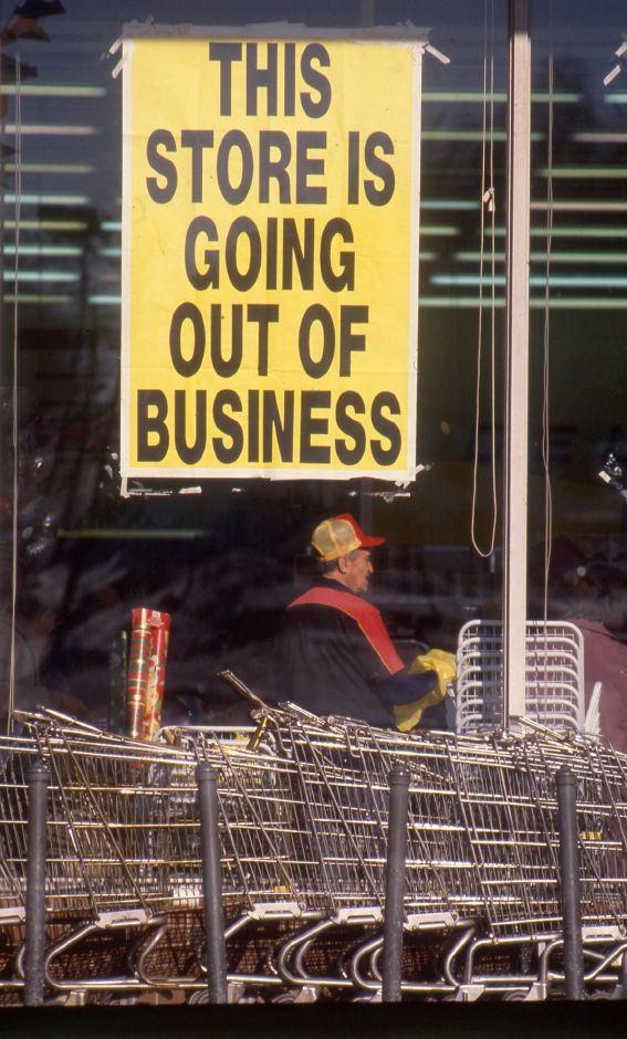 "RJ file photo - A Price Rite worker bags groceries inside the West Main Street store, Jan. 1990. ""Going out of business"" signs cover the front windows."