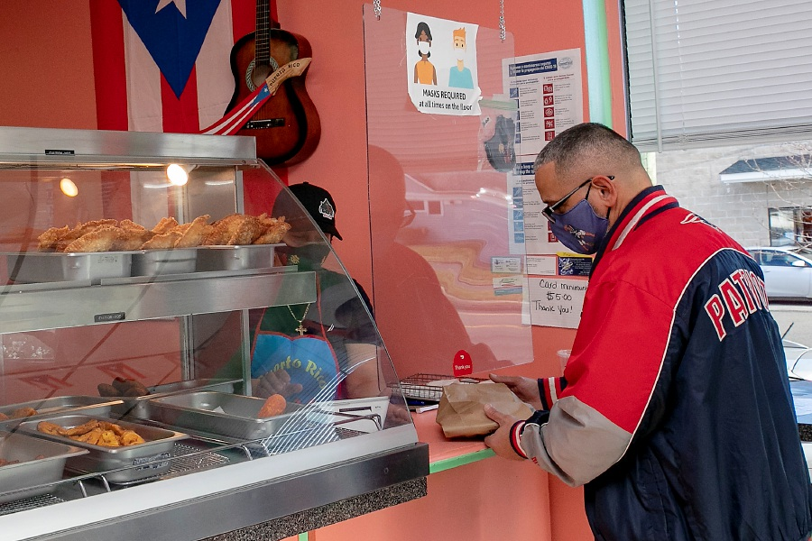 Customer Jason Rodriguez, of Meriden, picks up an order from server Tamara Gonzalez at El Jibarito Takeout, 620 E. Main St., Meriden, on Friday. With the restaurant industry being one of the most negatively impacted by the pandemic, businesses have had to generate new ideas to attract customers.