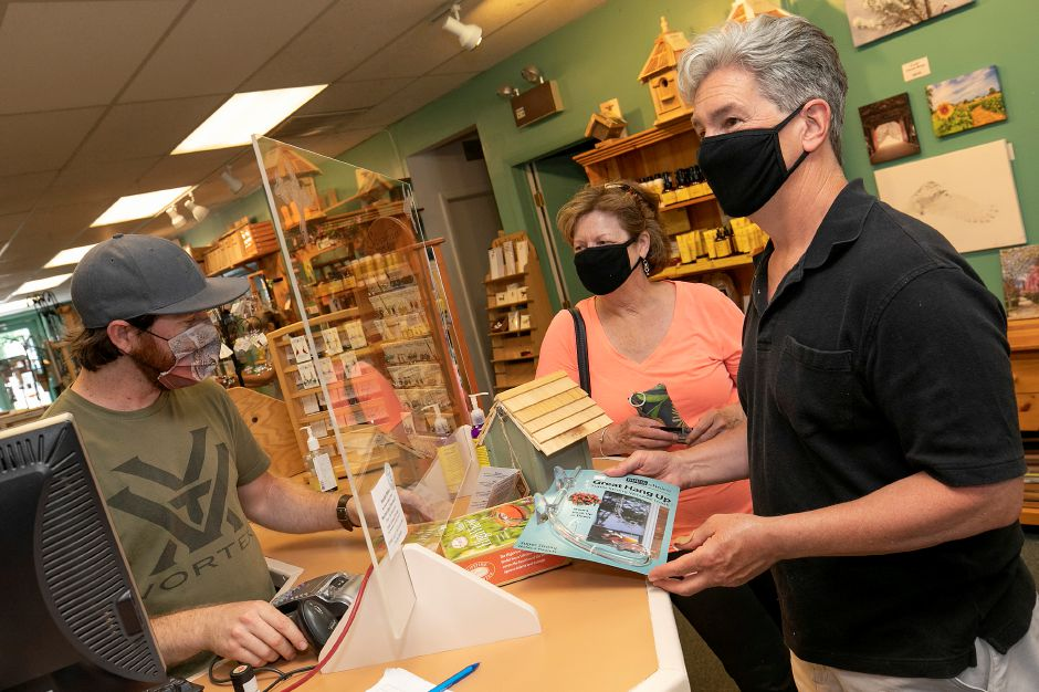 Ryan Zipp, co-owner of The Fat Robin Wild Bird and Nature Shop, left, helps customers Jim and Debbie Clifford, of Milford, with their purchase of a bird feeder.