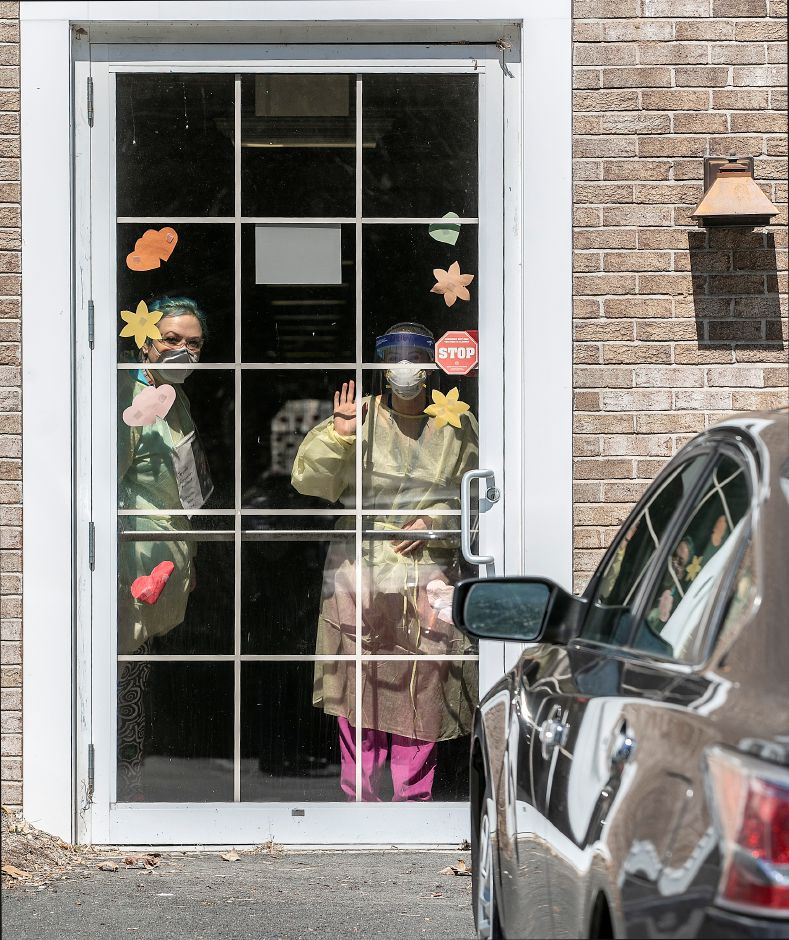 Workers wave from a door at Quinnipiac Valley Center on Kondracki Lane in Wallingford on April 15, 2020.