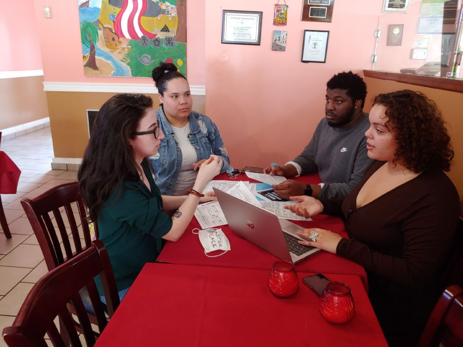 Bridging the Gap organizers, from left,  Katherine Conerera, Sierra Peele, Daishawn Whittingham and Kiara Nieves discuss details of voter registration for Saturday's rally on the Meriden Green. Mary Ellen Godin, Record-Journal