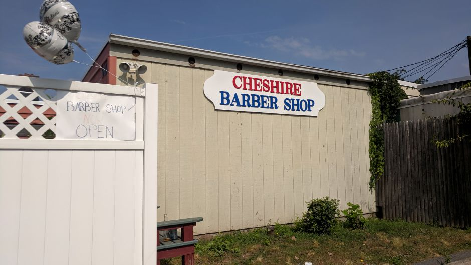 A handwritten sign and some balloons announce the reopening of Cheshire Barber Shop at a new location — behind Southend Wine & Spirits at 910B South Main St. | Michael Gagne, Record-Journal