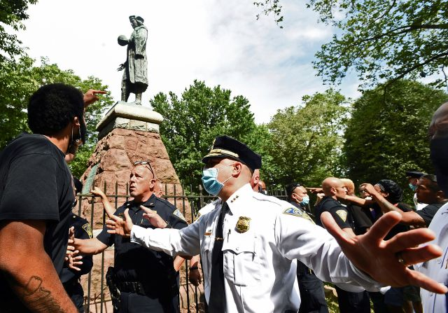 In this June 24, 2020 file photo, a man at left points to the statue of Christopher Columbus as police hold the crowd back before the statue was removed from Wooster Square Park, in New Haven, Conn. Disputes over what to do with statues of Christopher Columbus in Connecticut have resulted in both civil and criminal complaints. (Peter Hvizdak/Hearst Connecticut Media via AP, File)