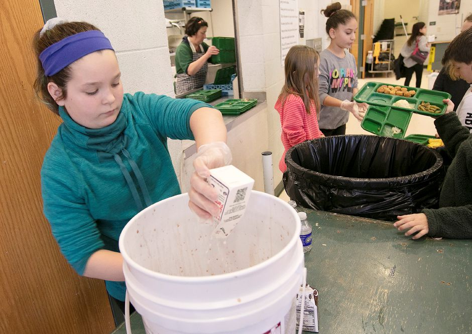 Fifth-grade student Leah Stewart, 10, empties a carton of milk into a receptacle as part of a lunch waste composting program at Thalberg Elementary School in Southington, Wed., Jan. 15, 2020. Leah is one of several members of the school