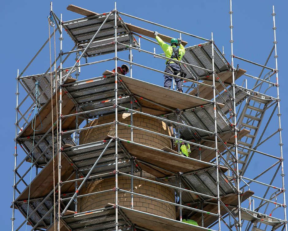 A worker lifts a board from a platform as crews from West Hartford based Advanced Scaffold Services dismantle the smokestack of the former Meriden-Wallingford Hospital on Cook Avenue in Meriden on Thursday. Dave Zajac, Record-Journal