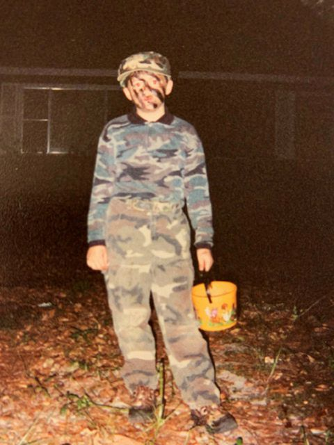 "This October 2001 photo provided by Paula Kovach shows her nephew, James Johnston as a boy dressed in camouflage for Halloween in Nacogdoches, Texas. As a toddler, Johnston liked to play in the triple-degree Texas summers in cargo shorts and heavy-duty camouflage, digging foxholes in his front yard. His mother, Meghan Billiot, recalls he once asked to have a toy driver's license created for him with the designation ""Special Forces"" and code name Silver Falcon. (Paula Kovach via AP)"