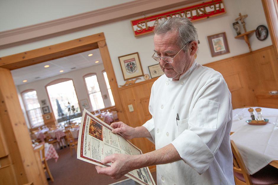 Markus Patsch, of Cheshire, owner of The Watch Factory Restaurant Austrian Country Cuisine, shows menu items at the business at 122 Elm St. in Cheshire, Tues., Feb. 19, 2019. Patsch is looking to retire and has put the restaurant up for sale. Dave Zajac, Record-Journal