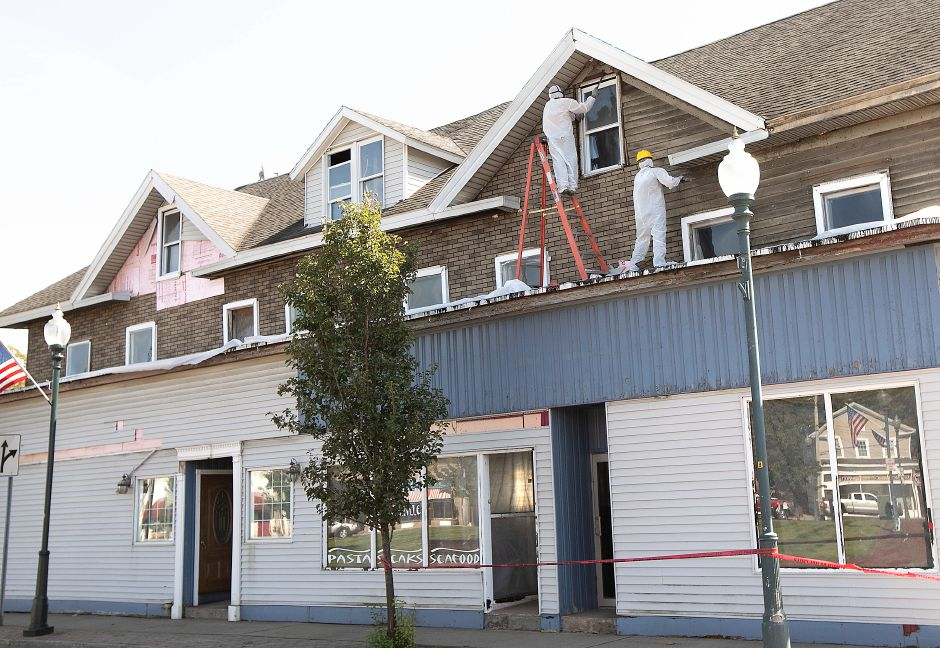 Crews from New Haven based LG Best Restoration LLC remove siding from the former T-Bonz Bar and Grill on Quinnipiac Street in Wallingford, Fri., Sept. 20, 2019. Dave Zajac, Record-Journal