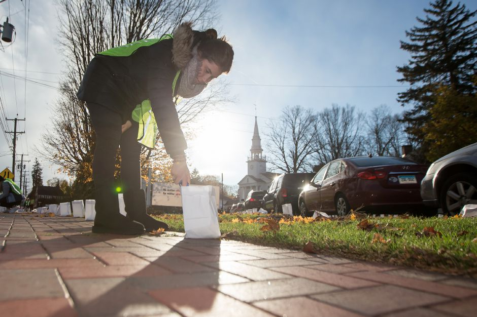 Elena Wbarra lights a luminary in front of the First Congregational Church Saturday during the 14th Annual Cheshire Lights of Hope to raise money for local charities in Cheshire November 10, 2018 | Justin Weekes / Special to the Record-Journal