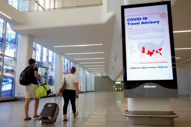 FILE - In this June 25, 2020, file photo, arriving travelers walk by a COVID-19 travel advisory sign in the baggage claim area of Terminal B at New York City