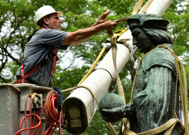 FILE- In this June 24, 2020 file photo, a worker prepares to remove the statue of Christopher Columbus from Wooster Square Park, in New Haven, Conn. Sculptures of the explorer were erected in the 19th and 20th centuries across the state, which has a large Italian-American population, but many were taken down in the summer of 2020, following widespread racial injustice protests that began following the killing of George Floyd at the hands of Minneapolis police. (Peter Hvizdak/Hearst...