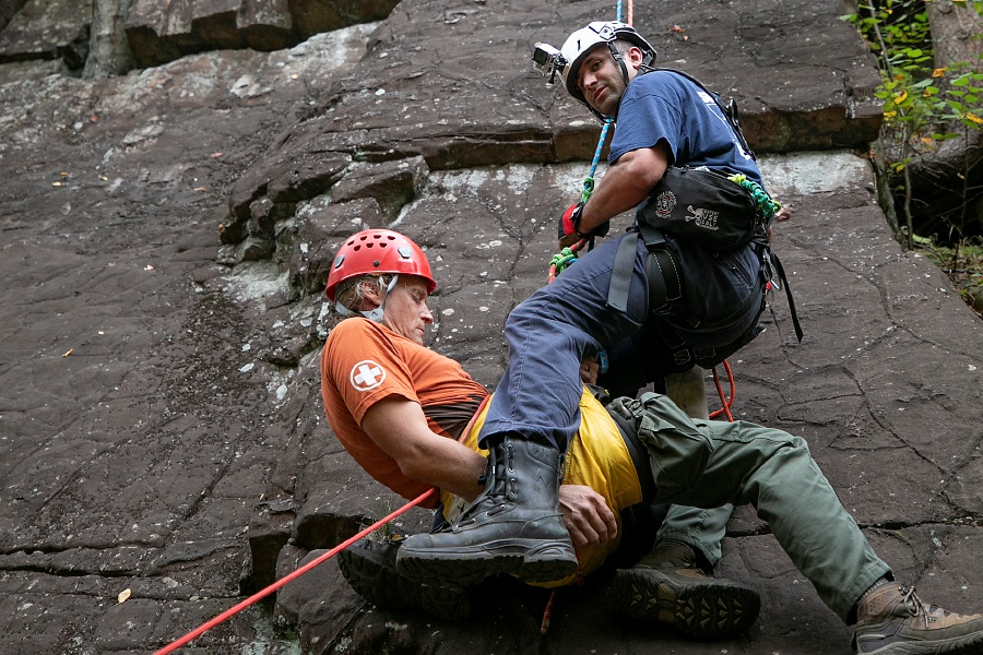 Above: Southington firefighter Daniel Comen, top, safely lowers Mike Mather, who acts as a fallen climber during a training exercise Tuesday on the main cliffs of Ragged Mountain in Southington. The Southington Fire Department received a FEMA grant that funded new equipment and training for rope rescues. Mather is a training instructor for Rhode Island-based Mather Rescue. Below: From left, Comen, Anthony Esteves, Lt. Andy Polzella and Mark Jurgilewicz carry  Mather.Photos by Dave Zajac, Record-Journal