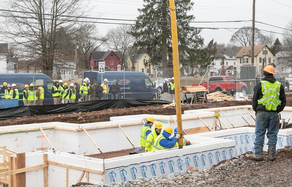 Senior students, left, from W.F. Kaynor Technical High School in Waterbury watch as crews pour cement into insulated concrete forms while working on the foundation of Hanover Place Veterans Housing on Hanover Street in Meriden, Mon., Jan. 13, 2020. Dave Zajac, Record-Journal