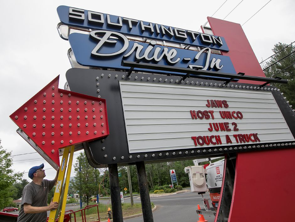 Crews from Sign Pro install the Southington Drive-In sign in June 2018. Dean Dube, installer, climbs a ladder to access electrical wiring inside the marquee.