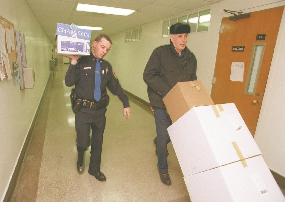 FILE: Police officer William Wright, left, and Robert Brady, of the traffic maintenance division, carry boxes of records from the Wallingford assessor