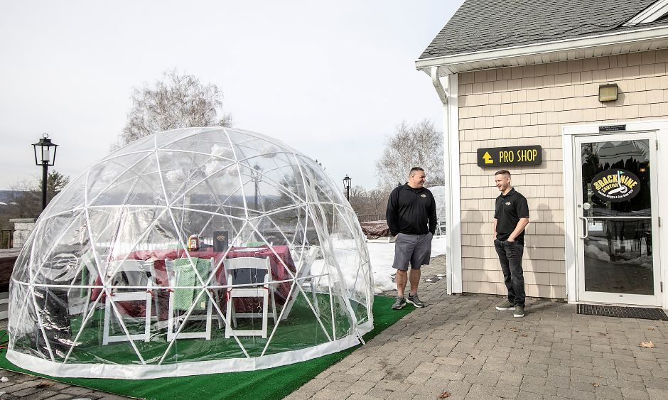 Managers Pete McAloon, left, and Mike Calvanese confer Thursday next to one of two igloos offered for dining at Back Nine Tavern at Southington Country Club. Dave Zajac, Record-Journal