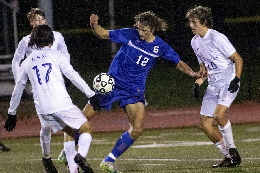 Southington's Cole Marek fights for the ball with Jack Joiner, left, and Luke Bushka of Lewis Mills during the second half at Southington High School on Thursday night. Lewis Mills won 2-1 in the season finale for both teams. Aaron Flaum, Record-Journal