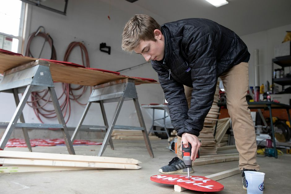 Mitchell Wollen, 16, of Wallingford, attaches a heart to a post Monday while making thank you signs in his garage. Wollen and family have been making and selling thank you signs to benefit local hospital and nursing home workers. Dave Zajac, Record-Journal
