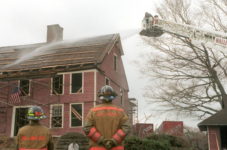 Firefighter Gene Letourneau, left and Firefighter John Andrews watch as the Wallingford fire department use their aerial truck in a training session to clean the Yale House April 4, 2000. The Yale House is being dismantled and moved to a new location.