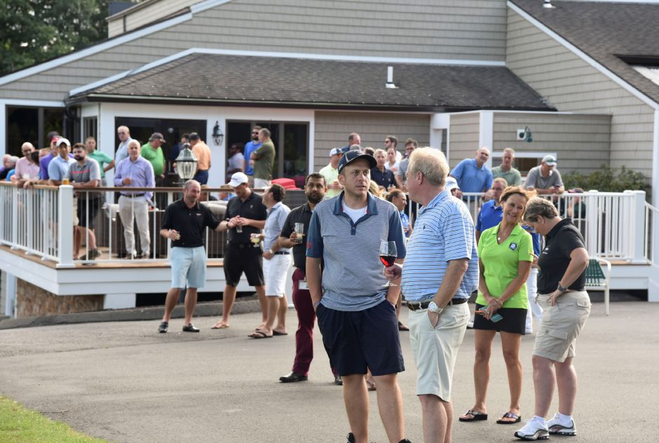 Spectators watch as an AirOcean Aviation helicopter drops dozens of golf balls from about 50 feet in the air onto The Farms Country Club fairway in Wallingford on Tuesday, August 21, 2018, as part of 34th annual Golf Classic at the Farms. Proceeds from the raffle will be donated to the Quinnipiac Business Education Foundation. | Bailey Wright, Record-Journal