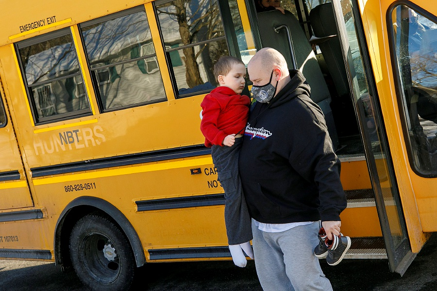 Frank Kish, of Meriden, picks up his five-year-old son Max from his Hanover Elementary School bus outside his residence on Feb. 8, 2021. Kish carries Max's sneakers since he often prefers not to wear them. Dave Zajac, Record-Journal