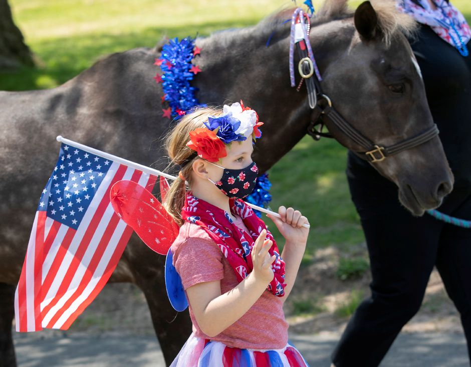 "Annika Paul, 8, of Unionville, dons her patriotic outfit next to pony ""Top Gun"" during a pony parade for patients and staff in honor of Memorial Day at Gaylord Specialty Healthcare in Wallingford, Thurs., May 21, 2020. The parade featured ponies from Pembroke Hill Equestrian and their owners and children that train at the Avon based stable. Dave Zajac, Record-Journal"