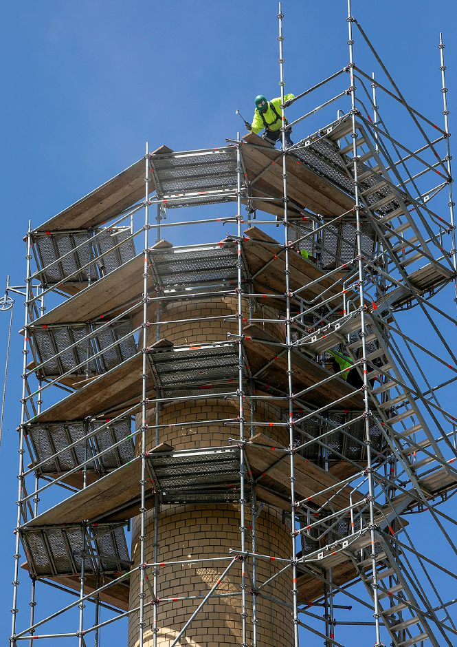 A worker uses the claw of a hammer atop a platform as crews from West Hartford based Advanced Scaffold Services dismantle the smokestack of the former Meriden-Wallingford Hospital on Cook Avenue in Meriden, Thursday, August 23, 2018. Dave Zajac, Record-Journal