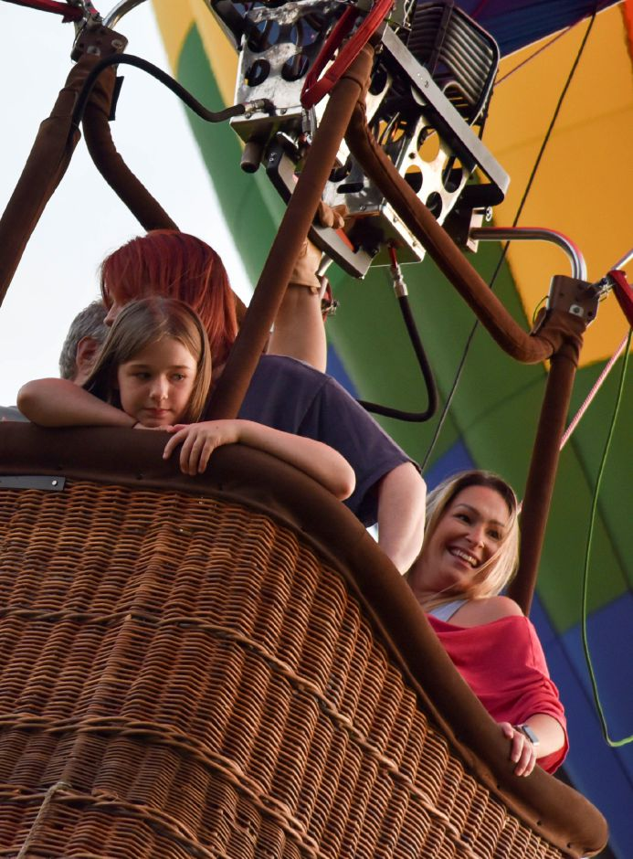 Plainville residents Ellie Keithan, front, rides a hot air balloon with mom Rosie Keithan and Melanie Ouellette during the first night of the 2019 Plainville Fire Company Hot Air Balloon Festival. | File photo